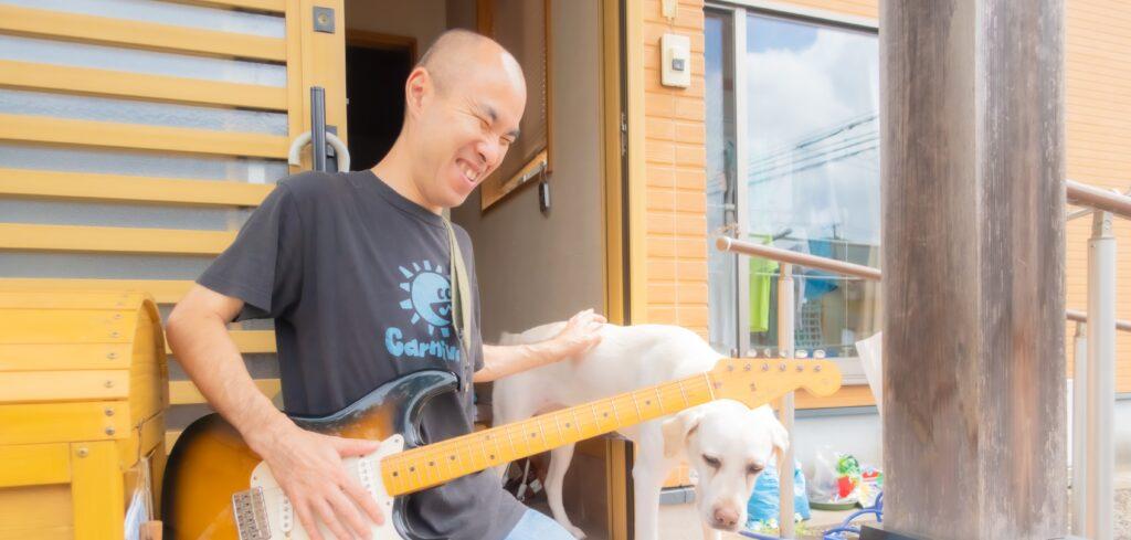ギターを持つ藏元さんと愛犬